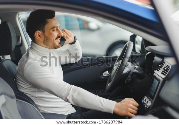 Un homme parle sur un téléphone portable en conduisant une voiture.