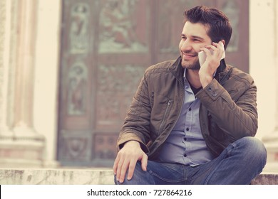 Man talking on a phone. Casual professional entrepreneur using smartphone smiling outside old building. Outdoor portrait of modern guy with mobile in the street