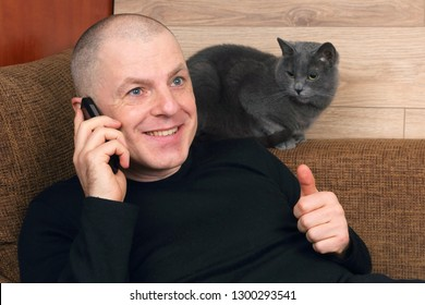 man talking on the phone resting on the couch next to a gray cat