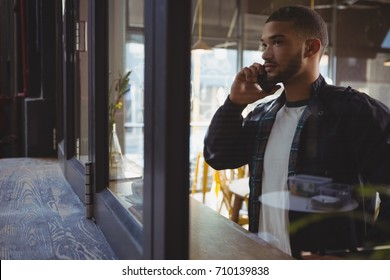 Man talking on phone seen through at window sill in cafe