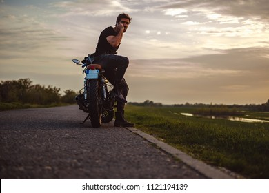 Man talking on the phone seriously while sitting on the bike in the middle of the road