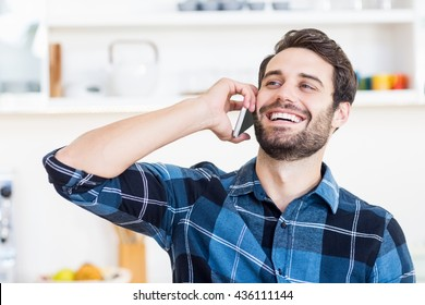 A man is talking on the phone and smiling at work