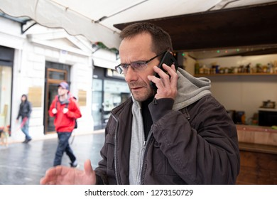 A man is talking on the phone and tries to solve a problem - front view on the streets