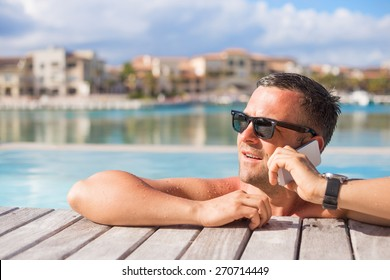 Man talking on phone while relaxing in the swimming pool
