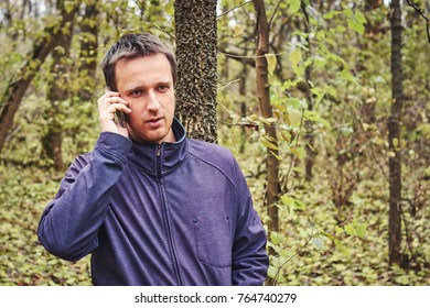 man is talking on the phone in the woods