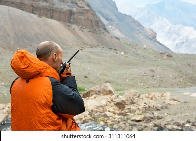 Man Talking on Radio. Mountain Rescue Officer Holding Radio Walkies Talkie and Severe Mountain Landscape Background