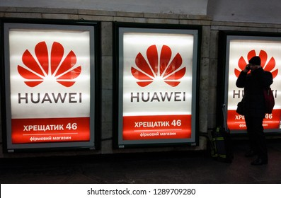 a man talking on a smartphone standing next to glowing Huawei logos with Huawei brand store advertising  in Kiev, Ukraine, 18 January 2019.