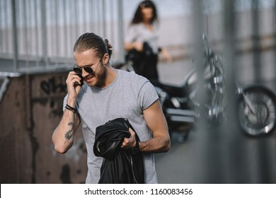 man talking on smartphone while girl standing with classical motorbike