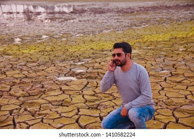 Man talking over cellphone sitting on a dried hard soil surface