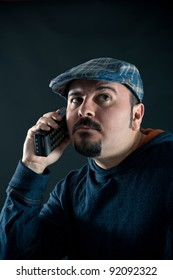Man talking at the phone against black background.