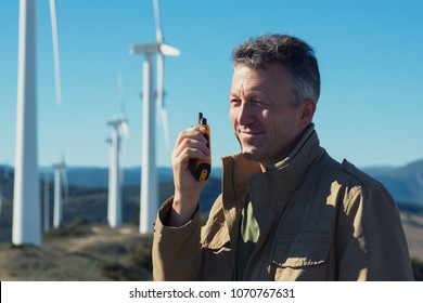 Man talking with portable radio transmitter outdoor over the wind turbines, image toned. Windmill generators. Wind power generators.