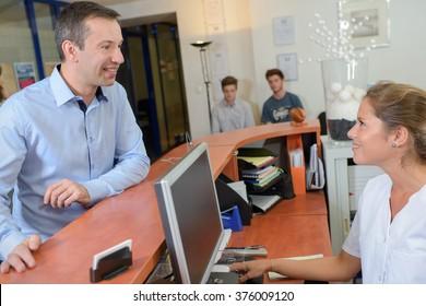 Man talking to receptionist