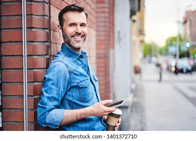 Man talking through wireless headphones while having coffee out in the city