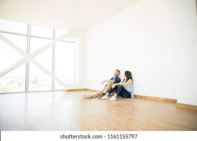 Man talking with woman while sitting on hardwood floor in empty room of new house