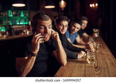 Man talks by the phone. Three sports fans in a bar watching soccer. With beer in hands.