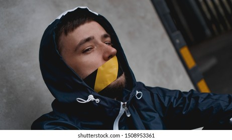 Man with tape over his mouth. The mouth is sealed with warning tape