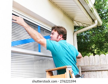 Man taping the windows on his home to protect from broken glass in a hurricane.