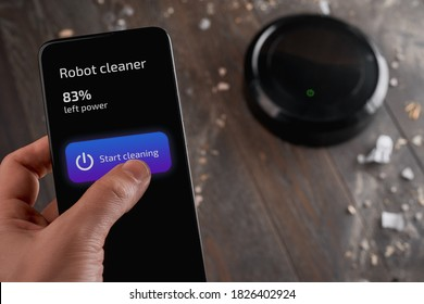 Man tapping a button on his phone and turning on a robot cleaner. Simple housework by one touch to your gadget.
