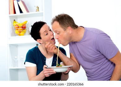 man tasting dinner from his wife