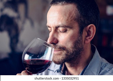 Man tasting a glass of red wine. Selective focus.