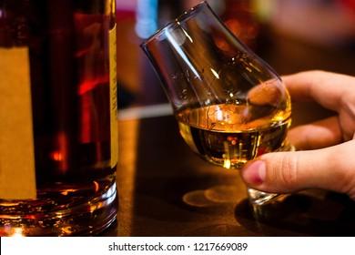 man tasting single malt whiskey from glencairn whiskey glass