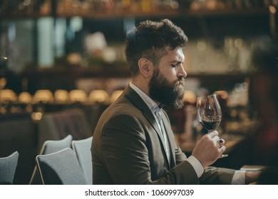 Man tasting wine in restaurant or bar interior