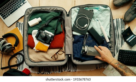 Man with tatted arm packs suitcase for adventure travel trip. Packing bag with camera, laptop, portable battery charger and electric toothbrush. Modern travel blogger concept