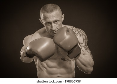 Man with tattoo boxing.Sepia