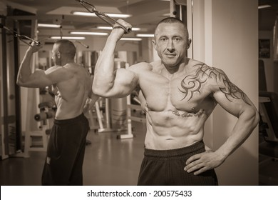 Man with tattoo in the gym.Sepia