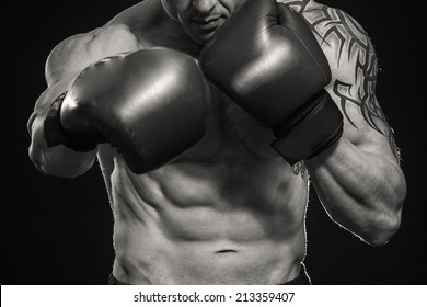 A man with a tattoo in red boxing gloves. Man boxing on black background. Boxer, boxing, tattoo, strength, punch, punching bag. - The concept of a healthy lifestyle.The idea for the film about boxing.