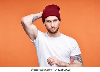 man with tattoos on his arms straightens his hat on his head on an orange isolated background