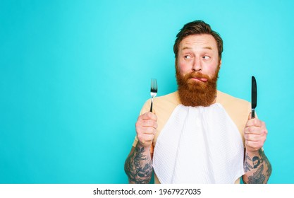 Man with tattoos is ready to eat with cutlery in hand. cyan background
