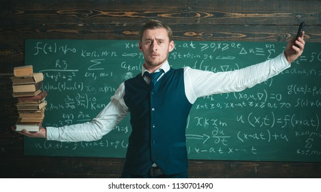 Man teacher balancing in hands pile of books and smartphone as analog and digital information storages. Teacher formal wear, chalkboard background. Smartphone smarter choice. Modern against outdated.