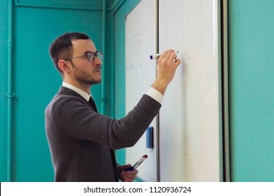 Man teacher in glasses writes on whiteboard in university classroom