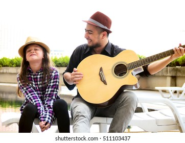 A man teaches girl to play guitar sitting at pool side. Soft focus on a warm summer evening.
