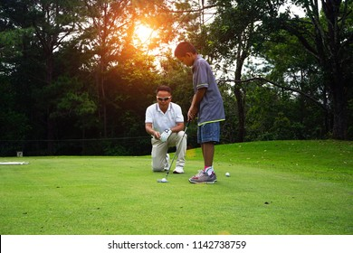 Man teaching Asian young to play golf while standing on field. Personal trainer giving lesson on golf course.