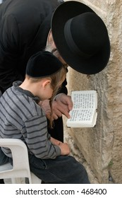 A man teaching a boy scripture.