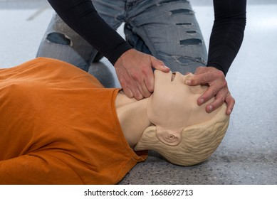 Man teaching cardiopulmonary resuscitation with a dummy on a white background. Opening airways and covering the nose to prepare air insufflations(Photo 10 of 18).
