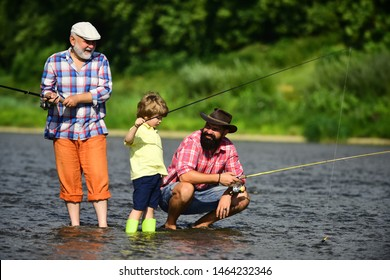 Man teaching kids how to fish in river. Father, son and grandfather fishing. Generations men. Three generations ages: grandfather, father and young teenager son