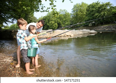 Man teaching kids how to fish in river
