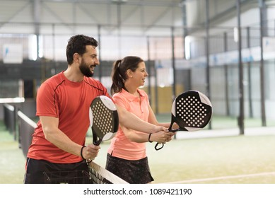 Man teaching woman how to play paddle tennis