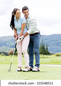 Man teaching woman how to play golf at the course