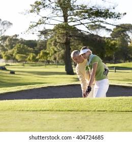 Man teaching a woman how to play golf