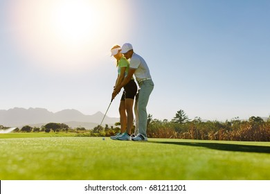 Man teaching woman to play golf while standing on field. Personal trainer giving lesson on golf course.