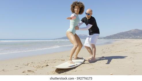Man teaching woman standing on surf
