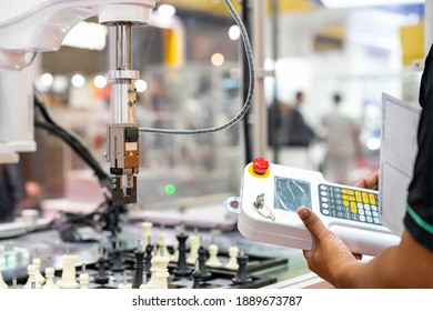 man technician enter command information pass wireless remote for control automatic robot arm for lift and place or moving chess pieces