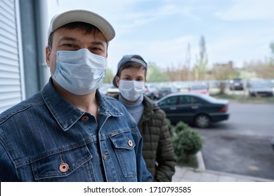 man and teen boy posing near wall and closed door of high-rise buildings with apartments, a residential area, a medical mask on their faces protects against viruses and dust
