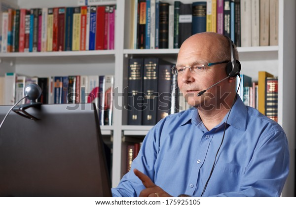 Man telephoning with computer, headset and webcam, copy space