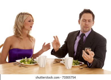 A man telling his date to hold on while he checks his phone for a text message.