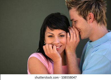 man telling a secret to his girlfriend
